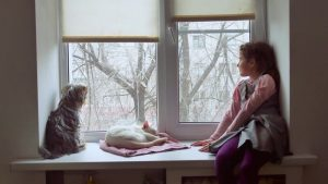 girl_with_her_pets_looking_out_the_window