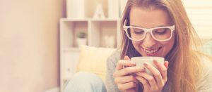 woman_sitting_drinking_her_coffee_on_her_couch