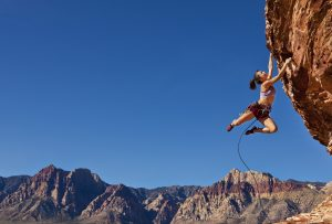 woman_rock_climbing_with_mountain_view_behind